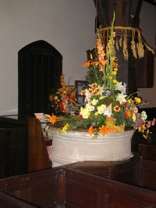 The font at St Oswald's decorated for Harvest